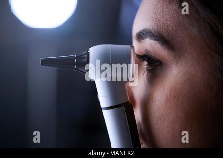 Female doctor using otoscope for examination, side view - Stock Photo