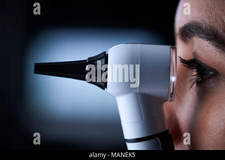 Female doctor using otoscope, side view, close up - Stock Photo