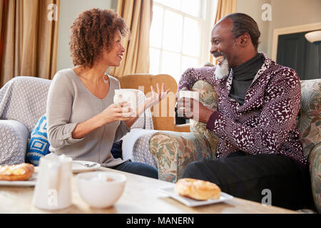 Middle Aged Couple Sitting Around Table In Coffee Shop - Stock Photo