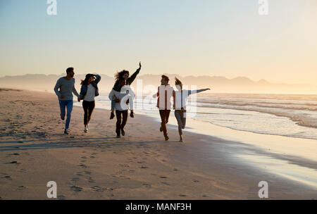 Group Of Friends Having Fun Running Along Winter Beach Together - Stock Photo