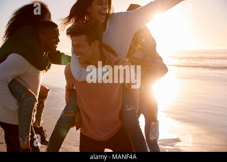 Group Of Friends Having Piggyback Race On Winter Beach Together - Stock Photo