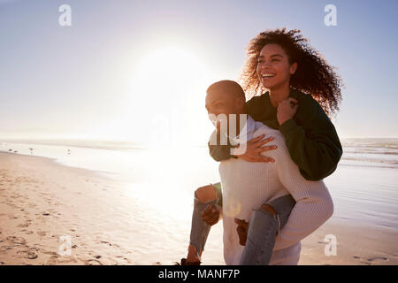 Man Giving Woman Piggyback On Winter Beach Vacation - Stock Photo