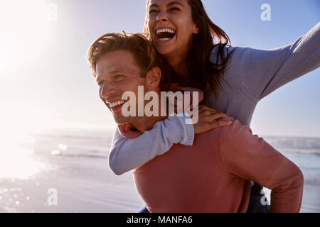Man Giving Woman Piggyback On Winter Beach Vacation - Stock Photo