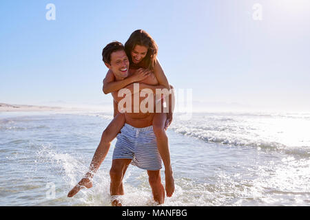 Man Giving Woman Piggyback On Summer Beach Vacation - Stock Photo