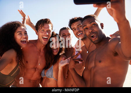 Group Of Friends Posing For Selfie Together On Beach Vacation - Stock Photo