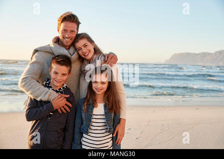 Portrait Of Family Walking Along Winter Beach Together - Stock Photo
