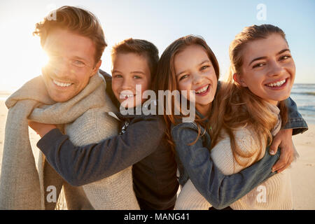 Parents Giving Children Piggyback Rides On Winter Beach - Stock Photo