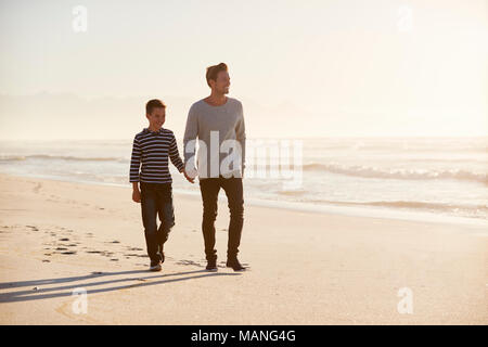 Father And Son Walking Along Winter Beach Hand In Hand - Stock Photo