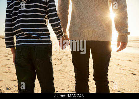 Detail Of Father And Son Walking Along Winter Beach Hand In Hand - Stock Photo