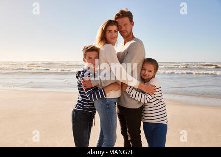 Portrait Of Loving Family Embracing On Winter Beach - Stock Photo