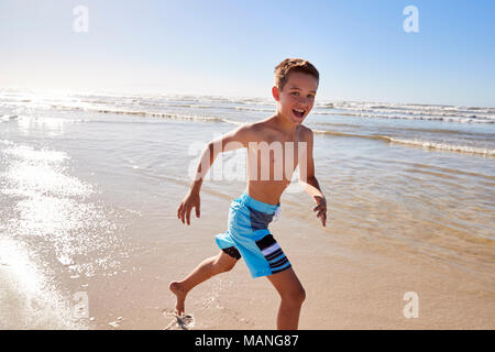 Portrait Of Boy Running Through Waves On Summer Vacation - Stock Photo