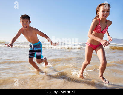 Boy And Girl On Summer Vacation Running Through Waves - Stock Photo