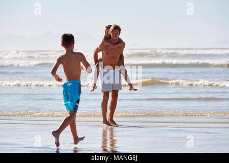 Father With Children Having Fun On Summer Beach Vacation - Stock Photo