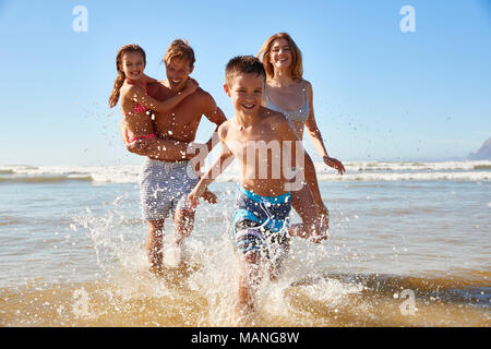 Family On Summer Beach Vacation Run Out Of Sea Towards Camera - Stock Photo