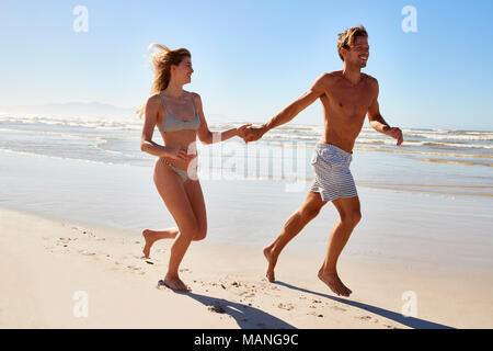 Couple On Summer Vacation Running Along Beach Together - Stock Photo