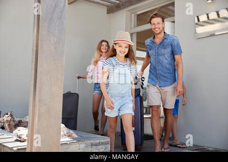 Portrait Of Family With Luggage Leaving House For Vacation - Stock Photo