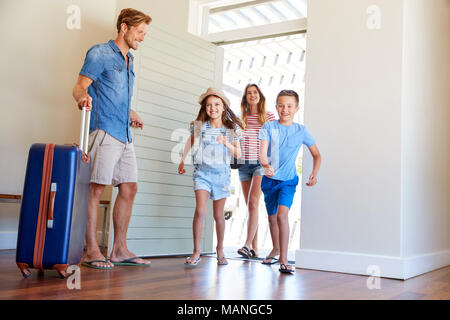 Family Arriving At Summer Vacation Rental - Stock Photo