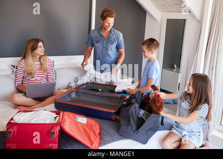 Family In Bedroom Pack Suitcases For Vacation And Use Laptop - Stock Photo