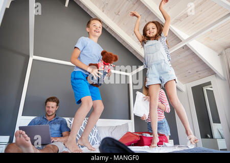 Excited Children Jump On Bed As Parents Pack For Vacation - Stock Photo