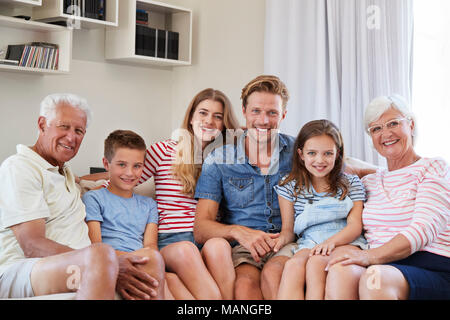 Portrait Of Multi Generation Family Sitting On Sofa At Home Stock Photo
