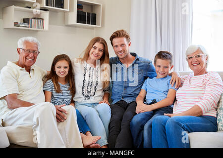 Portrait Of Multi Generation Family Sitting On Sofa At Home - Stock Photo