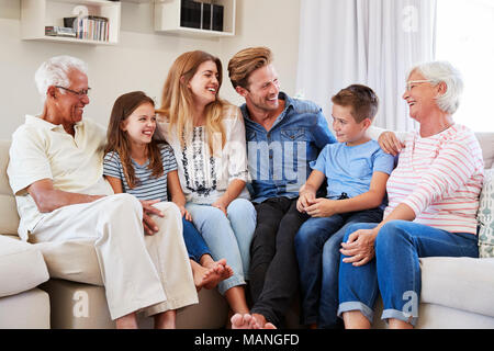 Multi Generation Family Relaxing On Sofa At Home Together Stock Photo