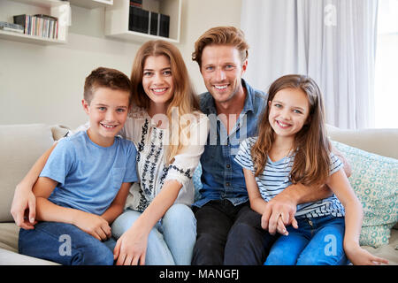 Portrait Of Smiling Family Sitting On Sofa At Home Together - Stock Photo