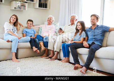 Multi Generation Family Sitting On Sofa At Home Watching TV - Stock Photo