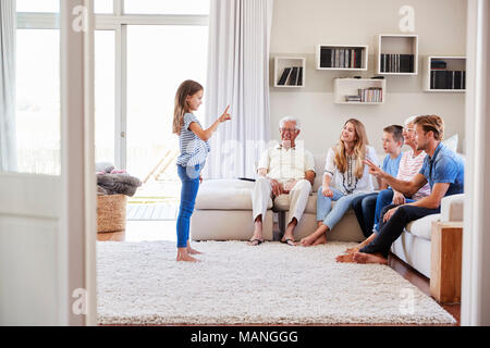 Multi Generation Family Sitting On Sofa At Home Playing Charades - Stock Photo