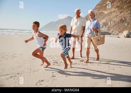 Grandparents Running Along Beach With Grandchildren - Stock Photo