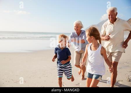 Grandparents Running Along Beach With Grandchildren On Summer Vacation - Stock Photo