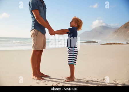 Father Holding Hands With Son On Summer Beach Vacation - Stock Photo