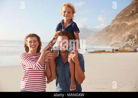 Portrait Of Parents Carrying Son On Shoulders On Beach Vacation - Stock Photo