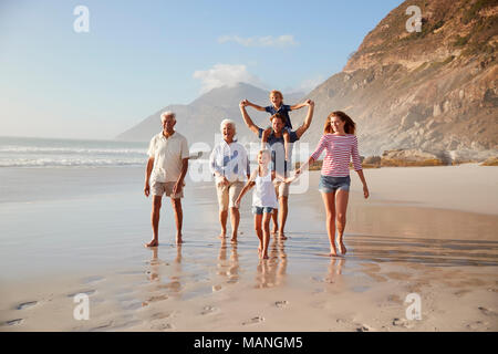 Multi Generation Family On Vacation Walking Along Beach Together - Stock Photo