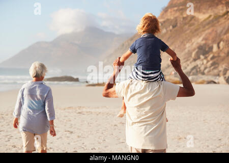 Grandparents Carrying Grandson On Shoulders On Walk Along Beach - Stock Photo