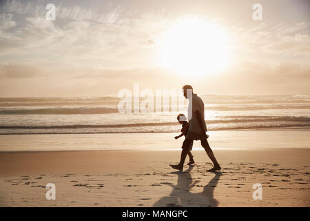 Silhouette Of Grandfather Walking Along Beach With Grandson - Stock Photo