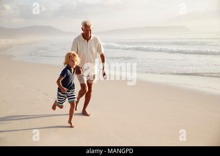 Grandfather Running Along Beach With Grandson On Summer Vacation - Stock Photo