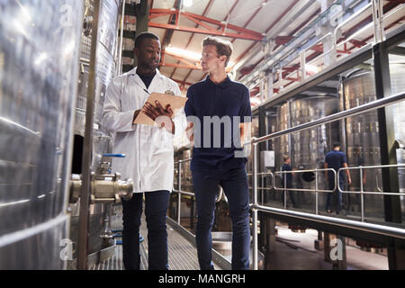 Two male staff members make an inspection at a wine factory - Stock Photo
