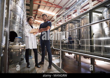 Male and female wine factory technicians looking to camera - Stock Photo