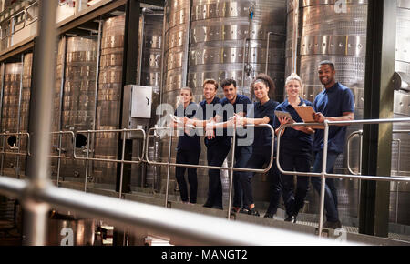 Staff at a wine factory smiling to camera from a gangway - Stock Photo