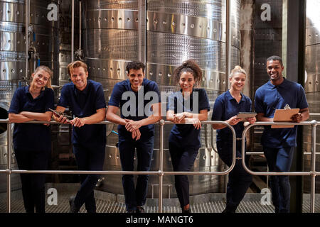 A row of staff at a wine factory smiling to camera, close up - Stock Photo