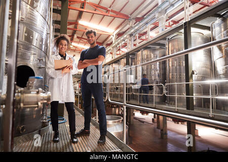 Male and female wine factory technicians smiling to camera - Stock Photo
