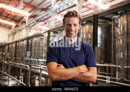 Portrait of a young white man working at a wine factory - Stock Photo