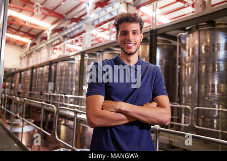 Portrait of a young Hispanic man working at a wine factory - Stock Photo