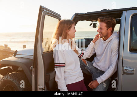 Young couple on road trip looking at each other by their car - Stock Photo