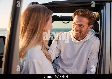 Young couple looking at each other by car, close up - Stock Photo