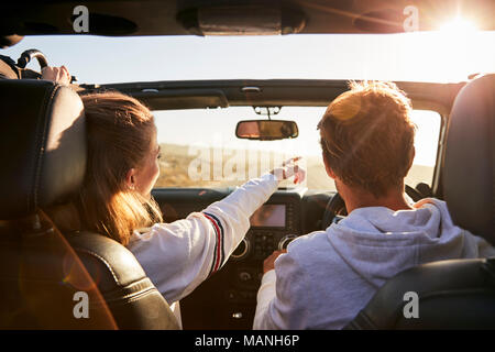 Young adult couple driving, woman pointing out directions - Stock Photo