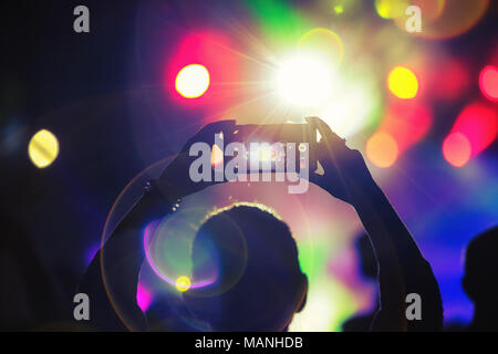Silhouette of a fan using smartphone to take a video at a concert - Stock Photo