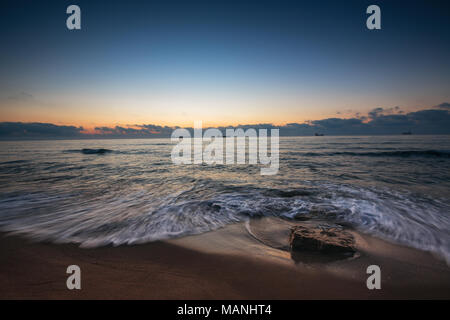Sunrise over the sea, rocks on the beach and sailing cargo ships in the water - Stock Photo