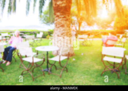 Cafe on a sea shore with green grass lawn, palm trees, tables and chairs for visitors. Blurred. - Stock Photo